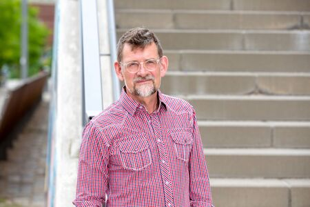portrait of handsome man in his 50s with plaided shirt standing at stairs