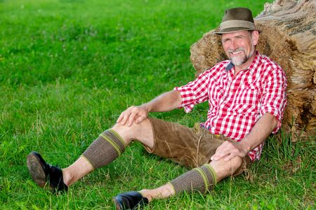handsome bavarian man sitting outdoors at tree stump and smiles