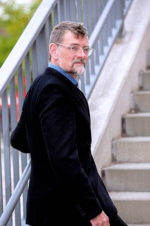 portrait of handsome businessman with eyeglasses walking up stairs 写真素材 - 130064161
