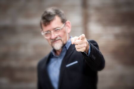portrait of handsome businessman pointing his finger to the camera