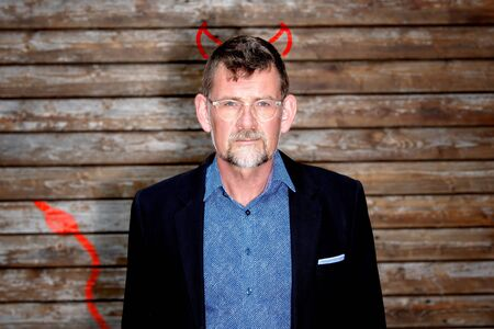 portrait of handsome businessman with drawn devils horns