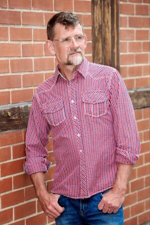 portrait of handsome bearded man in his 50s standing outside Stockfoto