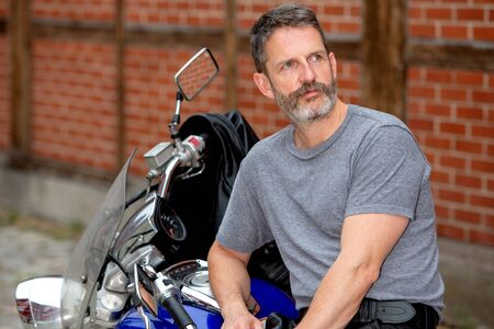 portrait of handsome man sitting on his bike outdoors