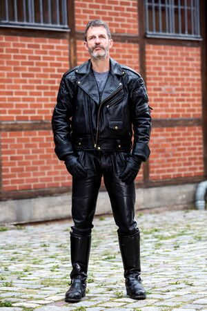portrait of handsome bearded man in leather jacket, pants and boots standing outside