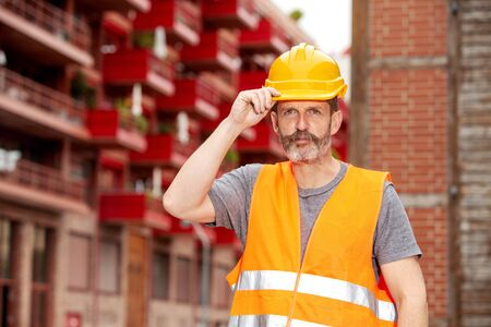 portrait of handsome construction worker with yellow helmet at construction site