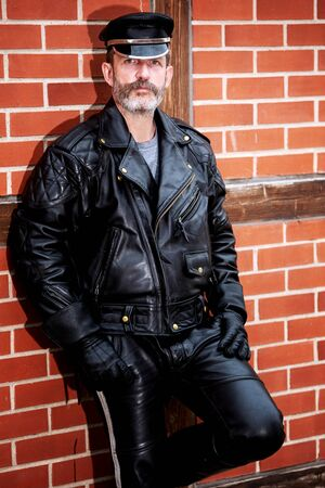 portrait of handsome sexy bearded man dressed in black leather leaning against brick wall Stock Photo