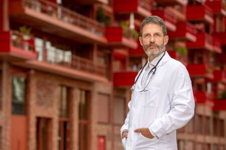 portrait of handsome bearded doctor in white coat standing outside