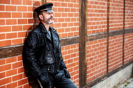 portrait of handsome sexy bearded man dressed in black leather leaning against brick wall 스톡 콘텐츠