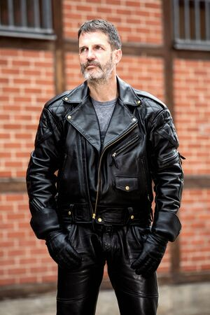 portrait of handsome bearded man in leather jacket and pants standing outside Stockfoto