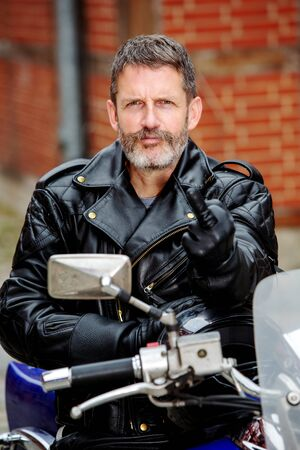 portrait of handsome man in black leather sitting on his motorbike and showing the middle finger
