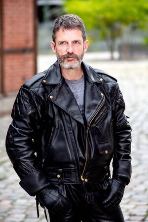 portrait of handsome bearded man wearing a black leather jacket and pants