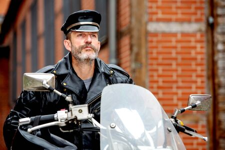 portrait of biker dressed in black leather sitting on his bike