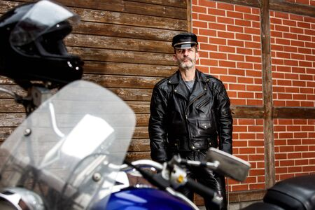portrait of sexy biker in black leather standing by his motorbike