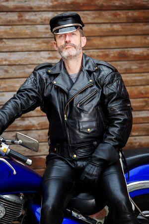 portret van een motorrijder gekleed in zwart leer zittend op zijn fiets