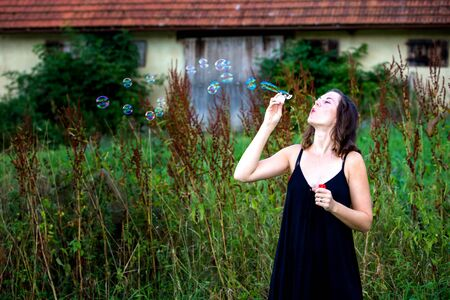 portrait of young brunette woman standing outdoors and blowing soap bubbles 写真素材