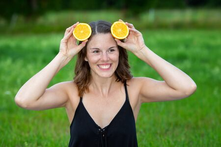 portrait of young woman outdoors holding slices of oranges to her head Stock Photo