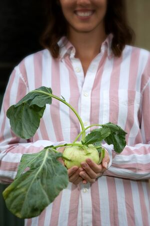 portrait of young brunette woman holding a turnip cabbage