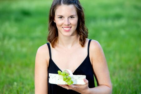portrait of young woman outdoors holding a basket with grapes Stock Photo