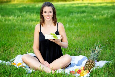 portrait of young woman sitting on blanket outdoors and holding basket with grapes Stock Photo