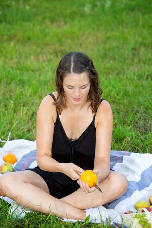 portrait of young woman sitting in park and cutting an orange Stock Photo