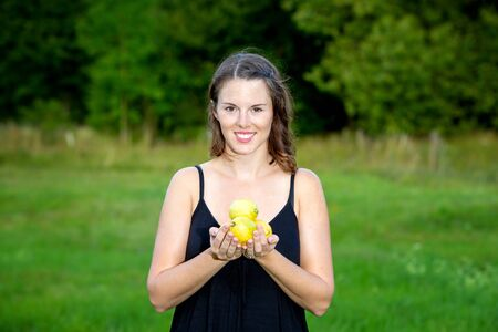 portrait of young woman standing outdoors in nature and holding lemons