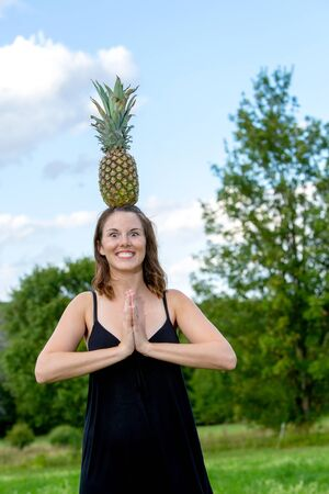 portrait of young brunette woman balancing a pineapple on her head Stock Photo