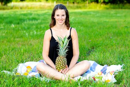 young brunette woman sitting outdoors and holding a pineapple Stock Photo
