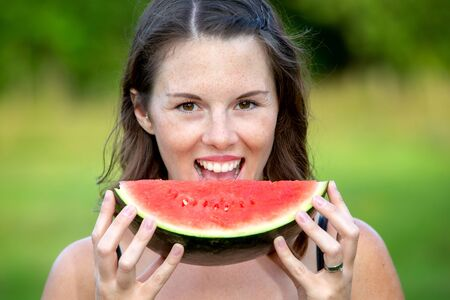 portrait of young brunette woman holding a slice of watermelon Stock Photo