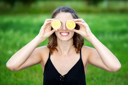 portrait of young woman holding a sliced lemon in front of her eyes Stock Photo