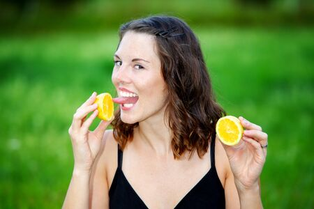 portrait of young woman outdoors holding a lemon and licking on it