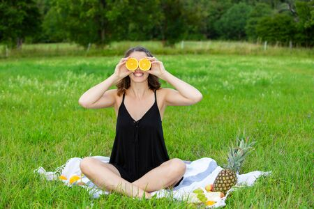 young woman sitting outdoors on blanket and holding slice of oranges in front of her eyes