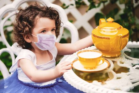 Little girl sitting in garden with cup and teapot and wearing a face mask