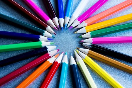 close-up of colored pencils in a circle on a grey background