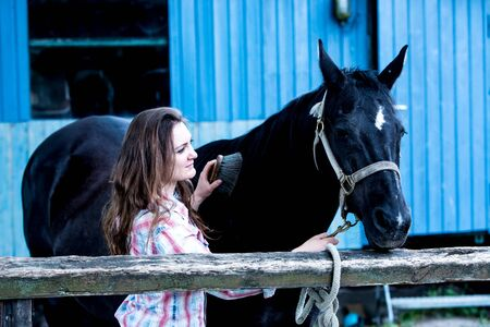 brunette young woman standing outdoors with her black horse Stok Fotoğraf