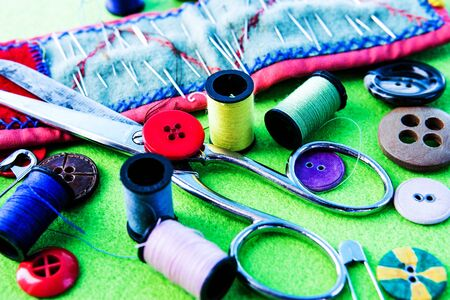 Yarn, scissors, needles and buttons on a green table