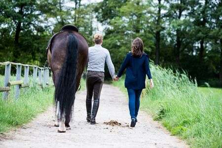 young couple walking along path outdoors with brown horse