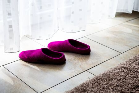 close-up of purple slippers on the floor by a white curtain
