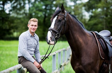 handsome man and his brown horse at a farm Imagens