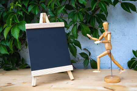 small chalkboard standing next to a wooden figure on wooden table Stock fotó