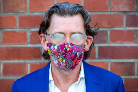 portrait of businessman wearing face mask with his glasses fooged up