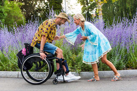 blond woman in a blue dress outdoors helping man in wheelchair to get up