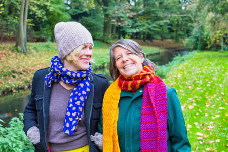 two women in their 50s hugging each other and walking in park in autumn