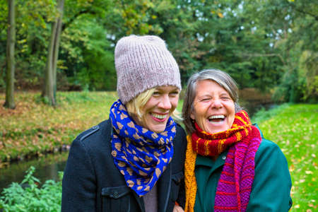 two women in their 50s hugging each other and smiling in a park in autumn