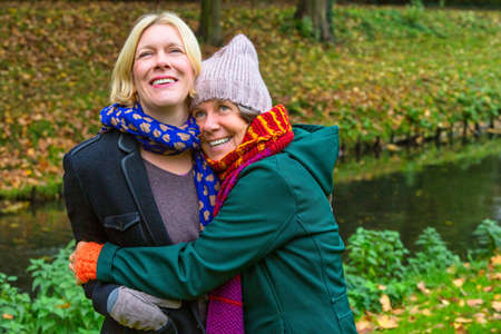 two women in their 50s hugging each other and smiling in park in autumn