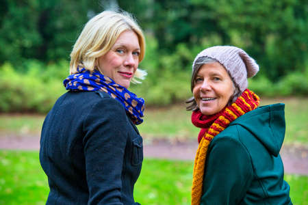 portrait of two women in their 50s standing in park in autumn Stockfoto