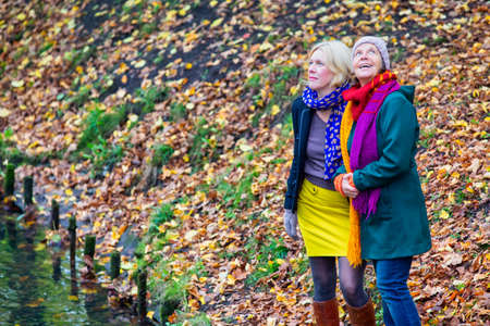 two women in their 50s hugging each other and standing in park in autumn