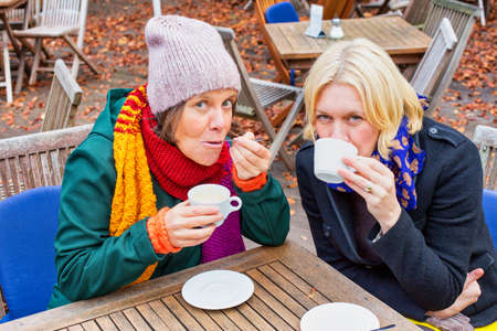 portrait of two women in their 50s sitting outdoor in autumn and drinking coffee