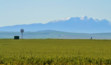 Landscape with windmill water pump and ceres mountains with snow photo