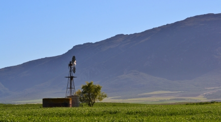 Landscape with hill and water pump windmill photo