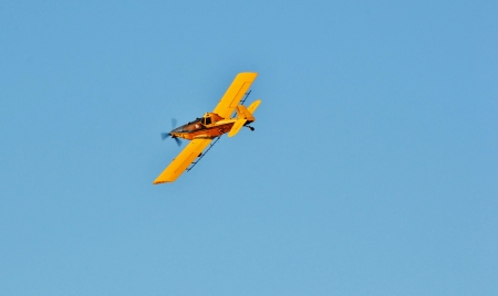 Yellow crop duster on blue cloudless sky photo